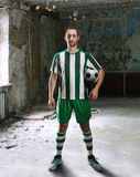 Football-player in a dirty room Royalty Free Stock Photo