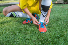 Football player getting ready for the game tying his shoes Royalty Free Stock Photo