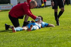 Football Player getting treatment. Physio helps a player with an injury Stock Photo
