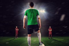 Football player in green with ball facing opposition Stock Image