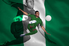 Football player in green kicking Stock Images