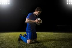 Football player happy after scoring goal. Young soccer player on knees holding a football after scoring a goal Royalty Free Stock Photos