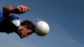 Football player heading the ball under blue sky stock footage