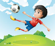 A football player in his red uniform kicking the ball royalty free illustration