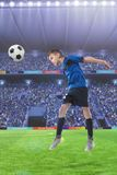 Football player hitting the ball with head on a soccer stadium. Football player hitting the ball with head on a soccer field royalty free stock photography