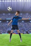 Football player hitting the ball with head on a soccer stadium. Football player hitting the ball with head on a soccer field stock photo