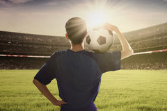 Football player holding ball on his shoulder Royalty Free Stock Photo
