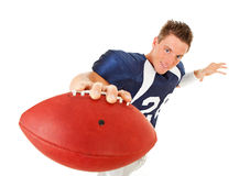 Football: Player Holding Ball To Camera. Caucasian American football player, in uniform, isolated on white, with various related props Royalty Free Stock Photos