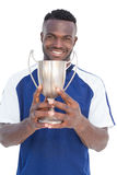 Football player holding winners cup Stock Images