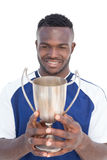 Football player holding winners cup Stock Photos