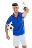 Football player holding winners trophy Royalty Free Stock Images