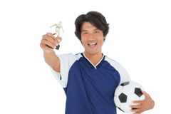 Football player holding winners trophy Stock Photo