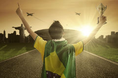 Football player holds a trophy at the street. Backside of football player celebrates his winning while raising a trophy with Brazilian flag on the street royalty free stock images