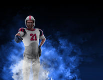 Football player. Illustration of a football player pointing his hand to the viewer, emerging from a cloud of fiery blue smoke Royalty Free Stock Images