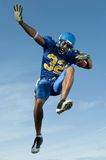 Football player jumping with ball Stock Images