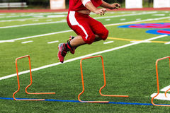 Football player jumping over orange hurdles, Stock Image