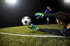 Goalkeeper trying to save a goal. Football player kick ball and goalkeeper try to catch the ball and save goal Stock Image