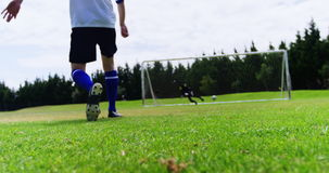 Football player kicking a ball in the field stock footage