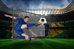 Football player kicking ball through tv Royalty Free Stock Photography