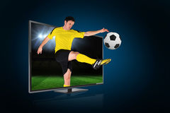 Football player kicking ball through tv Stock Photo