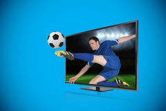 Football player kicking ball through tv Royalty Free Stock Images