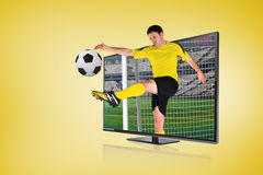 Football player kicking ball through tv Stock Photos