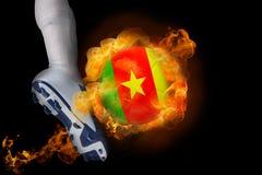 Football player kicking flaming cameroon ball Stock Photo