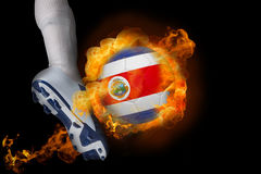 Football player kicking flaming costa rica ball Royalty Free Stock Images