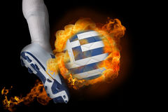 Football player kicking flaming greece flag ball Stock Photo