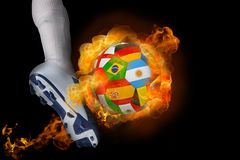 Football player kicking flaming international flag ball Royalty Free Stock Photos