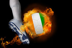 Football player kicking flaming ivory coast ball Royalty Free Stock Photos