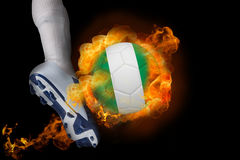 Football player kicking flaming nigeria ball Stock Photography
