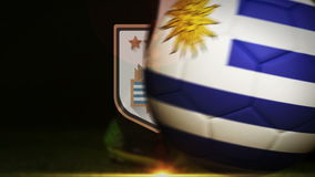 Football player kicking uruguay flag ball. On black background stock video footage