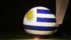Football player kicking uruguay flag ball. On black background in slow motion stock video footage