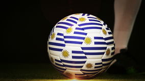 Football player kicking uruguay flag ball. On black background in slow motion stock footage