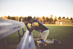 Football Player Kneeling Down To Pray On A Bench