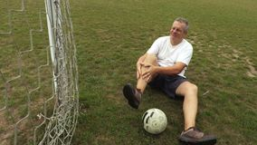 Football player with leg injury. In summer day stock footage