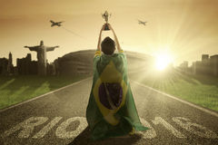 Football player lifts a trophy at the road. Football player with flag of Brazil, lifting a trophy while celebrate his winning on the road stock photo