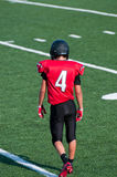 Football player looking down on the field from behind. Royalty Free Stock Images