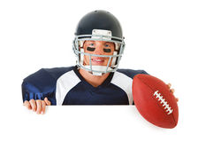 Football: Player Looking Over White Card. Caucasian American football player, in uniform, isolated on white, with various related props Royalty Free Stock Photos