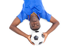 Football player lying on the ground holding ball with eyes closed Stock Photography