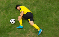 Football player lying injured on the pitch. Top View Football player in Yellow lying injured on the pitch Stock Photo