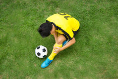 Football player lying injured on the pitch. Top View Football player in Yellow lying injured on the pitch Stock Images