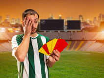 Football-player with penalties. Football player holds red and yellow cards standing on the football ground Royalty Free Stock Photos