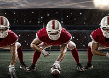 Football Player. S with a red uniform on the scrimmage line, on a stadium Royalty Free Stock Image