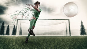 Football player playing. Football player shooting the ball and decompose . Splatter and dispersion effect Royalty Free Stock Image