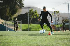 Football player practice dribbling on field. Young soccer player training in football field with team in background. Five a side football team practicing on stock image