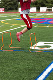 Football player at practice jumping over hurdles Stock Images