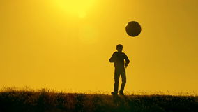 Football player practicing with the ball at sunset stock video