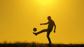 Football player practicing with the ball at sunset